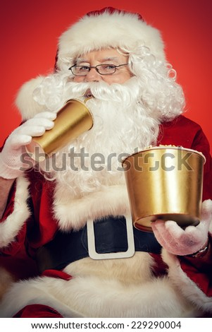 Close-up portrait of Santa Claus eating popcorn and drinking soda. Christmas. Red background. - stock photo