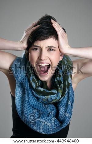 Close up portrait of screaming young short hair girl expression over gray studio background