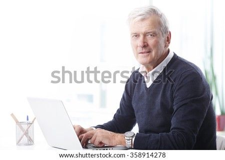 Close-up portrait of senior businessman typing on keyboard while working on new project at his laptop at office.