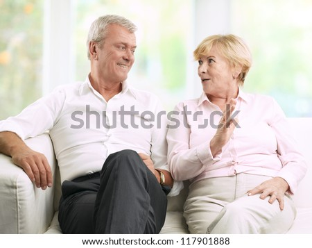 Close-up portrait of senior couple sitting on couch and talking - stock photo