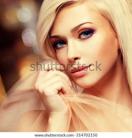 Close-up portrait of sensual young woman touching her face in the beige fabric on creative background. - stock photo