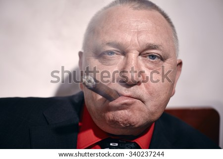 Close up portrait of serious middle aged businessman wearing black suit and red shirt smoking cigar in office - stock photo