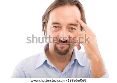 Close-up portrait of serious middle-aged man pointing at his forehead - stock photo