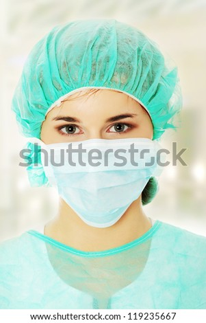 Close-up portrait of serious nurse or doctor in surgical mask
