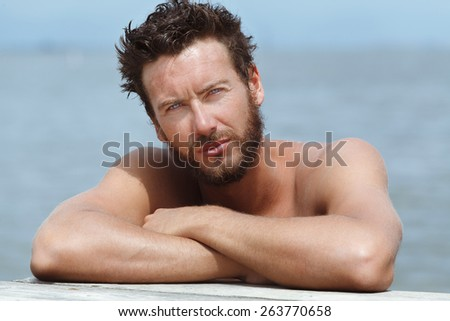 Close up Portrait of Sexy Athletic Handsome Man with No Shirt Posing at the Sea  - stock photo