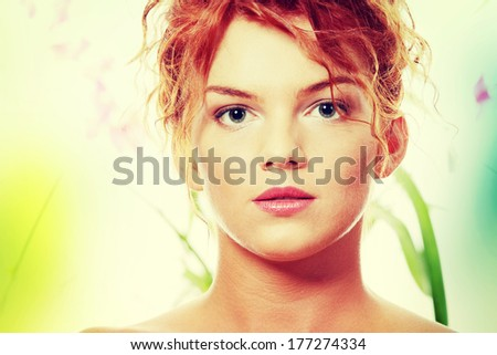 Close-up portrait of sexy caucasian young redhead woman against natural green background - stock photo