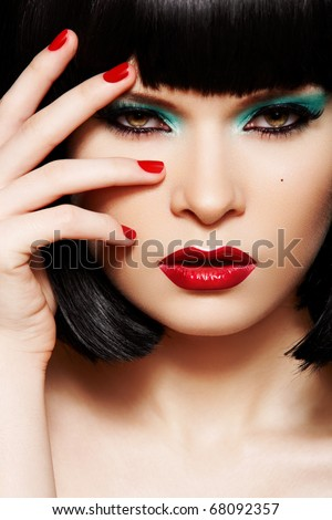 Close-up portrait of sexy european young woman model with retro glamour make-up and red bright manicure. Dark bob hairstyle, christmas makeup, green eyeshadows, bloody red lips with gloss