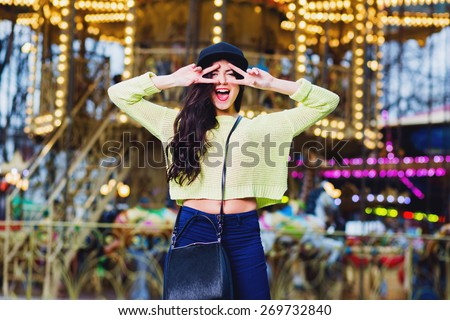 Close up portrait of sexy  fancy stylish woman have fun and smile on attractions. Wearing trendy hipster swag black hat and neon  sweater . Have perfect body and bright make up. - stock photo