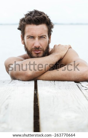 Close up Portrait of Sexy Handsome Man with beard and No Shirt Posing at the Sea  - stock photo