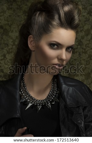 close-up portrait of sexy young brunette with gothic rock style, posing with brown modern hair-style, leather jacket and rock necklace. Looking in camera  - stock photo