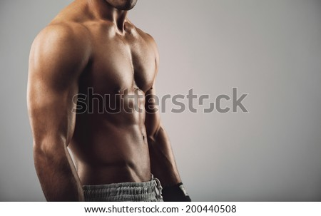 Close up portrait of shirtless young man standing on grey background. Man with muscular body. Health and fitness concept with copyspace for your text. - stock photo