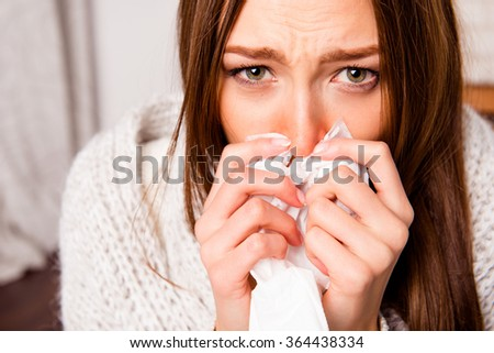 Close up portrait of sick woman  with fever sneezing in tissue - stock photo