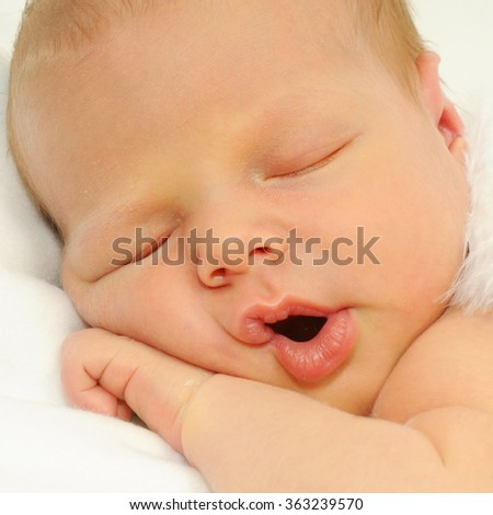 close up portrait of sleeping newborn baby with his hand under his chubby chick and his mouth open