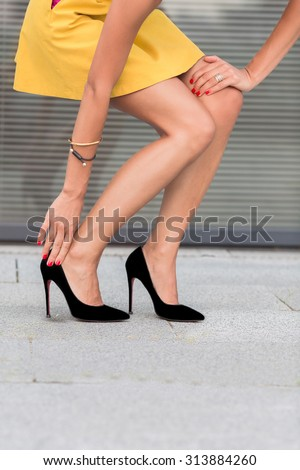 Close-up portrait of slim and slender woman's legs on high heels. Fashion lady in little yellow dress walking in the city centre. - stock photo