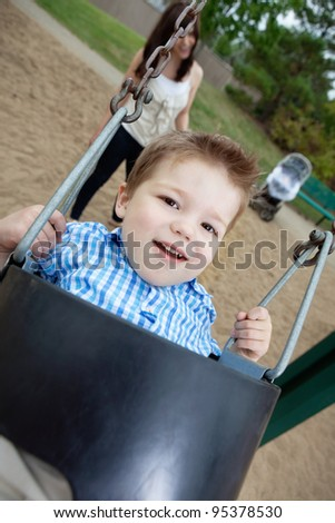 Close-up portrait of small boy swinging while mother standing in background - stock photo
