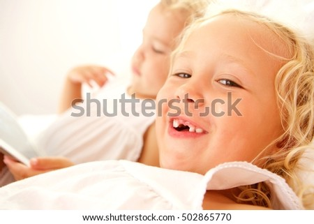 Close up portrait of smiling adorable girl on bed with sister using digital tablet in background.