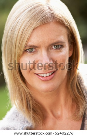 Close Up Portrait Of Smiling Blonde Woman Outdoors - stock photo