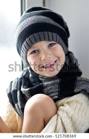 Close-up portrait of smiling boy wearing knitted hat