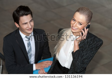 Close up portrait of smiling businesswoman with smart phone and partner. - stock photo