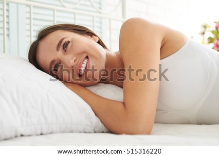 Close-up portrait of smiling charming woman lying on the bed. Morning, good start of the day