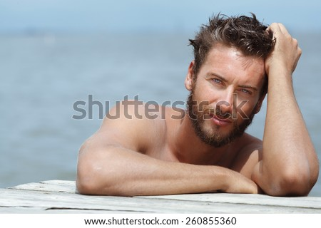 Close up Portrait of Smiling Gorgeous Handsome Man with No Shirt Posing at the Sea  - stock photo