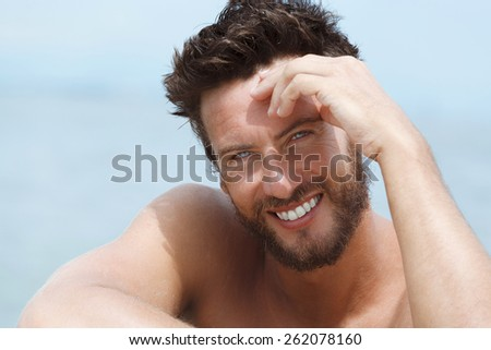 Close up Portrait of Smiling Handsome Man with No Shirt Smiling at the Sea  - stock photo