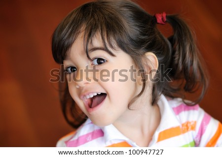 Close up portrait of smiling little girl with ponytail hairstyle