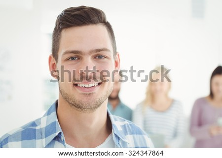 Close-up portrait of smiling man standing at office - stock photo
