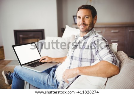 Close-up portrait of smiling man using laptop while sitting on sofa at home - stock photo