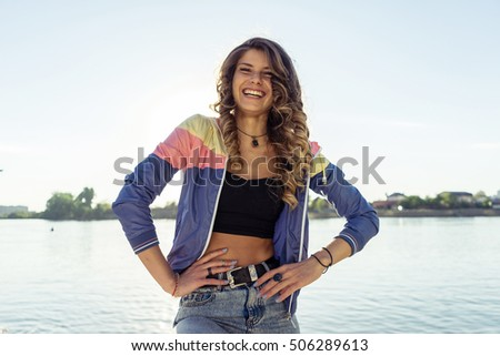 Close up portrait of smiling pretty sexy woman with beautiful eyes, sensual fresh happy face, positive emotions, sports figure , shining smile, curl,hipster dressed,natural background