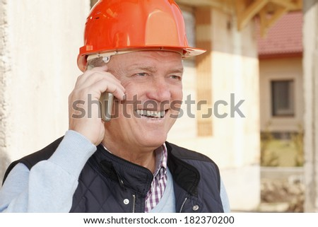 Close-up portrait of smiling senior construction architect while using mobile phone - stock photo