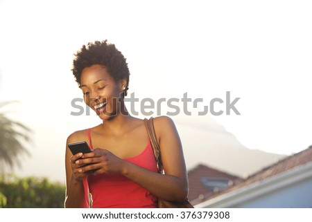 Close up portrait of smiling young african woman standing outdoors and reading text message on her mobile phone - stock photo
