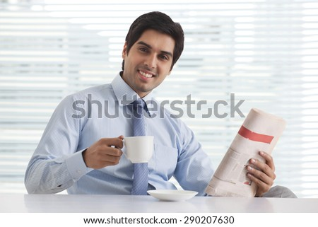 Close-up portrait of smiling young business executive enjoying tea with newspaper in office - stock photo