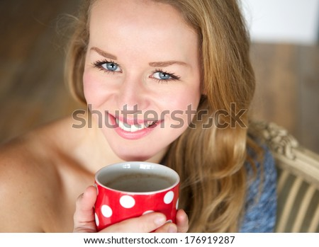 Close up portrait of smiling young woman holding coffee cup at home