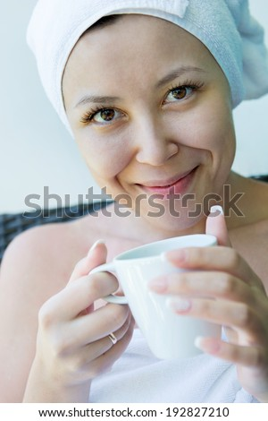 Close-up  portrait of Smiling Young woman in the towel hat  with the cap of coffee at home  - stock photo