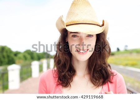 Close up portrait of smiling young woman standing in cowboy hat outside - stock photo