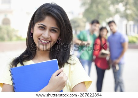 Close-up portrait of smiling young woman with friends in the background - stock photo