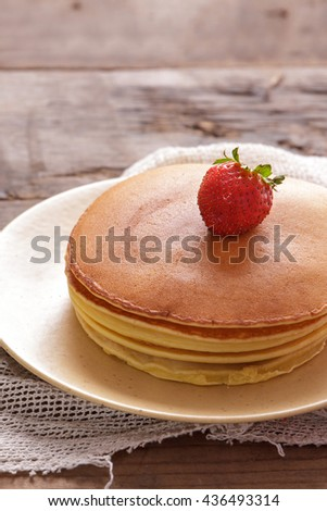 close up portrait of stack of delicious pancake with strawberry topping