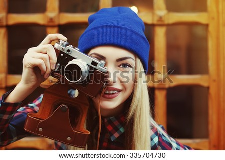 Close up portrait of stylish happy smiling hipster girl in  braces with vintage camera. Model looking at camera. City lifestyle.  Toned - stock photo