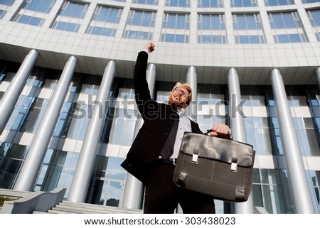 Close-up portrait of successful businessman with his arm up. Man in black suit posing with brief case isolated on office building.