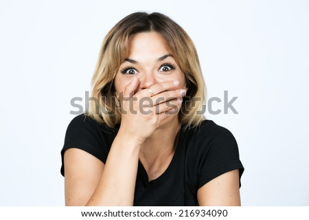 Close-up portrait of surprised attractive woman covering her mouth by the hands, over white background - stock photo