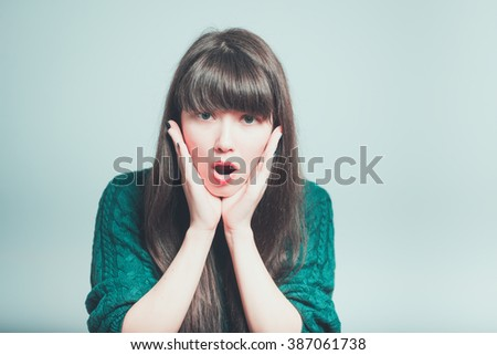 Close-up portrait of surprised beautiful girl holding her head in amazement and open-mouthed. Over gray background. - stock photo
