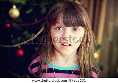 Close-up portrait of surprised little girl under Christmas tree, softening filter applied - stock photo