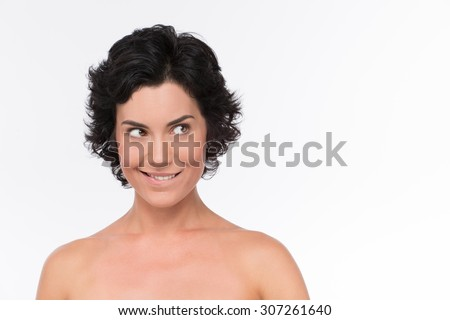 Close-up portrait of surprised middle-aged woman looking with amazement and little smile. Nude brunette looking left with surprise. - stock photo
