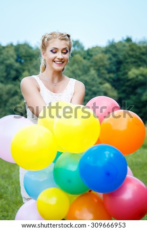 Close-up portrait of sweet young pretty blonde girl with colored make-up with many colorful balloons