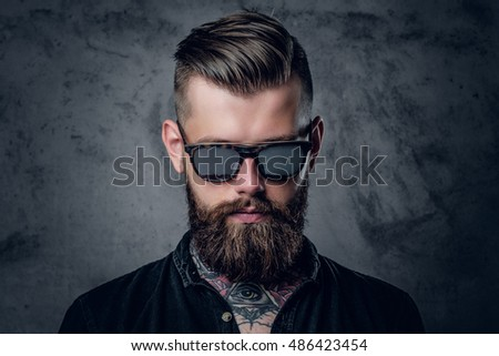 Close up portrait of tattooed, bearded hipster male in sunglasses.
