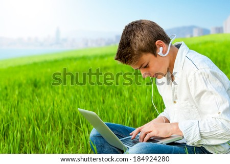 Close up portrait of teen boy working on laptop in green field and city in background. - stock photo