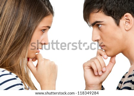Close up portrait of teen couple looking at each other with wondering expression.Isolated on white. - stock photo