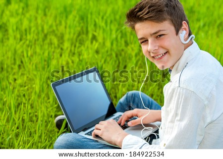 Close up portrait of teen student working on laptop in green grass field.