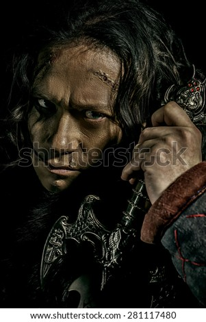 Close-up portrait of the ancient male warrior in armor holding sword. Historical character. Fantasy. - stock photo